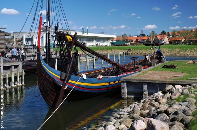 Reconstruction of a Viking longship, tarred and painted red, yellow, and blue. The Viking Ship museum in Roskilde is visible in the background.