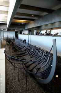 Photograph of Skuldelev 1, a wide bodied trading vessel. partially intact.