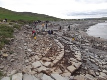 Tomb on the beach at Swandro - the outer walls of the Neolithic chambered tomb are the concentric circles in the foreground, the burial chamber is under the grass at the left. The Atlantic Ocean is lapping at the edge of the site. Courtesy of the Swandro-Orkney Coastal Archaeology Trust'
